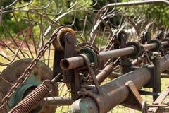 Oud roestig Hay Turner Oude landbouwmachine op hooi Stock Foto's
