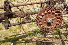 Oud roestig Hay Turner Oude landbouwmachine op hooi Stock Fotografie