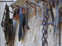 Oud roestig hulpmiddel op een oude hangerhaak stock fotografie