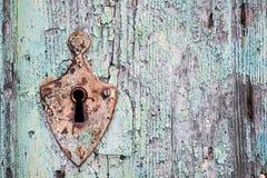 Oud roestig metaalslot en sleutelgat op een oude turkooise houten deur Stock Foto's
