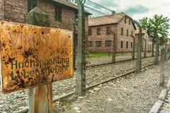 Oud roestig plaatwaarschuwingsbord die op elektrische omheining met binnen prikkeldraad wijzen bij het Naziconcentratiekamp van A royalty-vrije stock foto's