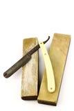 Oud roestig scheermes en twee scherpende stenen Stock Foto