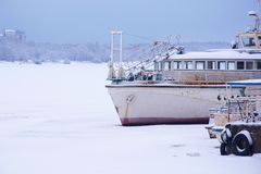 Oud roestig schip in de winter bij de pijler stock foto's