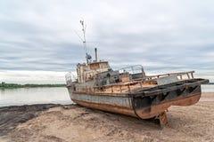 Oud roestig schip op zandstrand tegen rivierpanorama bij dageraad Stock Afbeelding