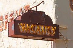 Oud roestig vacatureteken op een motelgebouw stock foto's