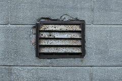 Oud roestig ventilatietraliewerk op gepleisterde muur Stock Afbeelding