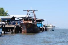 Oud roestig vissersvaartuig in gedokte haven Stock Foto