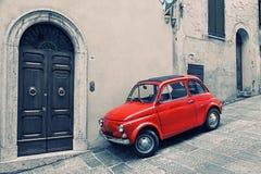 Oud rood Fiat 500 R om zich dichtbij een muur te bevinden Royalty-vrije Stock Foto's