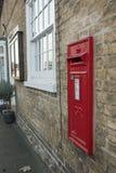 Oud, rood geschilderd die brievenvakje in de muur van een privé huis in een Engels dorp wordt gezien stock foto