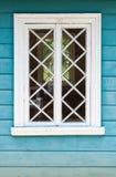 Oud Russisch huisfragment, blauwe muur en wit venster Stock Foto
