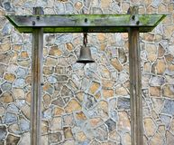 Oud Rusty Bronze Metal Bell Hanged op een Groene Bemoste Houten Pijler in een Muur van het Steenpatroon stock fotografie