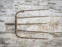 Oud Rusty Pitchfork Head op een Schuurmuur royalty-vrije stock foto's