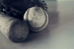 Oud ruw en ruw honkbal en uitstekende houten knuppel op blauwe textuurachtergrond stock foto's