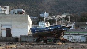 Oud schip die in haven blijven Oude boot Het werkt niet Roestmetaal Schepen in dok Stadsgebouwen op heuvel Boom op gebied stock videobeelden
