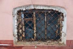 Oud sjofel klein herenhuisvenster met roestig rooster royalty-vrije stock afbeelding