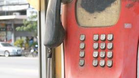Oud sjofel rood telefoontoestel op een stadsstraat Uitstekende telefoon in de telefooncel stock footage