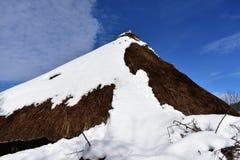 Oud sneeuwdiepallozahuis met steen en stro wordt gemaakt Dakclose-up met sneeuw, blauwe hemel wordt behandeld die Piornedo, Lugo, royalty-vrije stock foto
