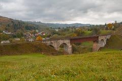 Oud spoorwegbrug en bergdorp carpathians stock foto