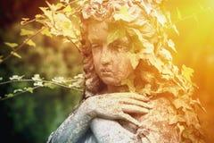 Oud standbeeld van droevige engel in klimop Geloof, godsdienst, onsterfelijkheidconcept royalty-vrije stock fotografie