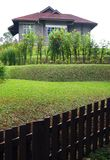 Oud steenhuis met terrasvormige tuin en omheining Stock Afbeelding