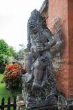 Oud steenstandbeeld bij tempelpoort Taman Ayun Stock Afbeelding