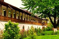 Oud stijl rustiek huis met afmattende houten portiek en voor groene tuinboom royalty-vrije stock afbeeldingen