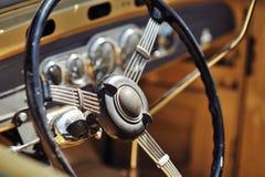 Oud stuurwiel in een uitstekende retro auto Stock Afbeeldingen