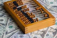 Oud telraam op een stapel van dollars royalty-vrije stock afbeelding