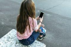 Oud tienermeisje 9-11 jaar, zittend in een stadspark in de zomer, die een smartphone in haar handen houden, die communiceren royalty-vrije stock afbeelding