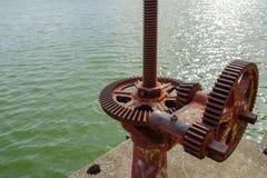 Oud toestel en geroest tandradmechanisme, het wiel van het radertjetoestel voor water stock foto