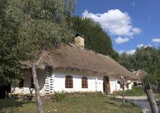 Oud traditioneel Oekraïens landelijk huis met met stro bedekt dak en rieten omheining in de tuin Stock Fotografie