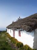 Oud traditioneel wit plattelandshuisje met met stro bedekt dak stock foto's