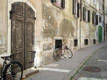 Oud uitstekend beeld met roestige grijze muur en twee fietsen Stock Fotografie