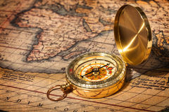 Oud uitstekend gouden kompas op oude kaart Stock Afbeelding