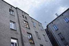 Oud uitstekend grijs krottenwijkhuis met beschadigde muren en uitgestoten hemel op achtergrond royalty-vrije stock afbeeldingen