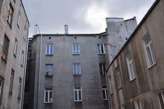 Oud uitstekend grijs krottenwijkhuis met beschadigde muren en uitgestoten hemel op achtergrond Stock Afbeelding