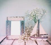 Oud uitstekend houten kader, witte bloemen en varende boot op houten lijst wijnoogst gefiltreerd beeld zeevaartlevensstijlconcept stock foto