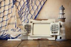 Oud uitstekend houten wit kader, vuurtoren en varende boot op houten lijst wijnoogst gefiltreerd beeld zeevaartlevensstijlconcept Royalty-vrije Stock Afbeelding