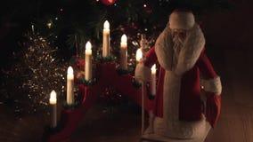 Oud uitstekend stuk speelgoed die van Santa Claus zich dichtbij elektrische kaarsen en Kerstmisboom bevinden stock footage