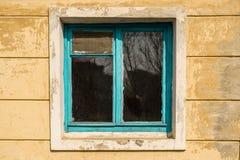 Oud venster in een verlaten huis met blauw houten kader stock afbeeldingen