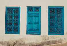 Oud venster met blauwe blinden op vuile witte muur Stock Foto