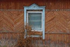 Oud venster met een gordijn op een bruine houten muur van een landelijk die huis met droge vegetatie wordt overwoekerd stock fotografie