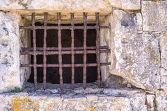 Oud venster met een roestig rooster op steenmuur Stock Foto