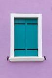 Oud venster met lichtblauwe blinden op lichte violette muur stock foto