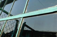Oud venster met ongewassen ruit en doen barsten raamkozijnpai stock foto