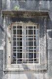 Oud venster met rooster in uitstekende muur stock afbeeldingen