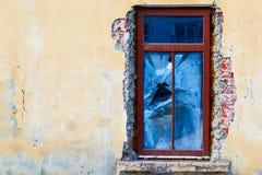 Oud verbrijzelingsvenster op een verlaten oud gebouw Gebroken venster op de gele muur Oude en vuile muur van het binnenland van o Stock Afbeelding