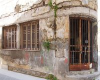 Oud verlaten verlaten commercieel eigendom op een hoek met afbrokkelende gebarsten sjofele muren en roestende ijzerbars over de d stock afbeeldingen