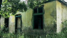 Oud verlaten en vernietigd huis in een berg onder bomen stock footage