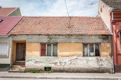 Oud verlaten huis met gebroken en beschadigde die vensters in de stad door leeftijd wordt geruïneerd stock afbeelding